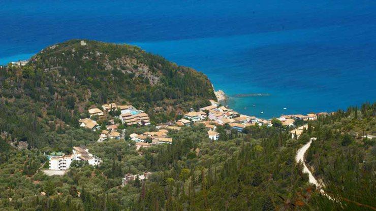 Blick von der natürlichen Bergwelt auf griechisches Dorf mit Strand und Meer