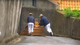 Ein Paar genießt eine traditionelle Korbschlittenfahrt
