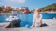 Junge Dame sitzt am Wasser vor einem Motorboot und blickt auf das bunte Fischerdorf Assos