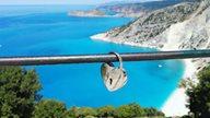 Liebesschloss hängt an Brücke mit Panoramablick auf den Myrtos Beach