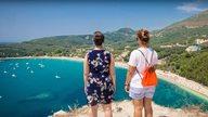 Zwei Frauen genießen die Aussicht auf einen griechischen Hafen und das Meer
