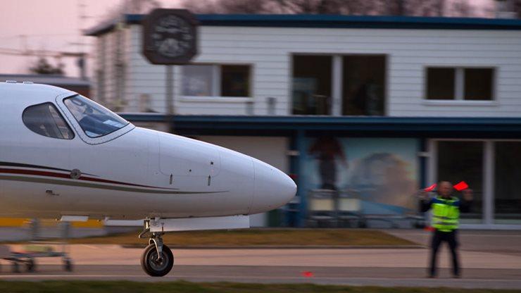 Kleines Flugzeug wird von einer Sicherheitskraft am Flughafen eingewiesen