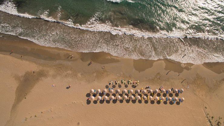Griechischer Sandstrand auf Kefalonia mit Sonnenschirmen und leichtem Wellengang