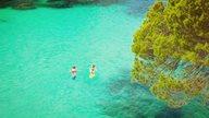 Ein Paar erkundet eine türkisblaue Bucht