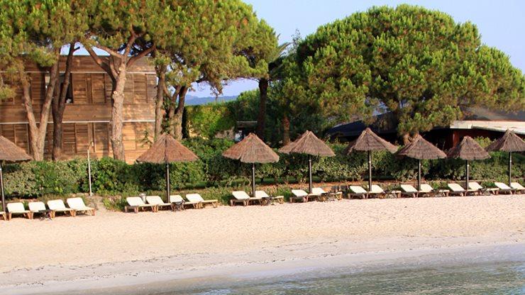 Hotel am Sandstrand mit Sonnenliegen und Schirmen