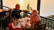 Paar genießt Abendessen bei Sonnenuntergang mit Blick aufs Meer