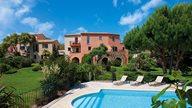 Große grüne Gartenanlage mit Pool, Liegen und Ferienwohnungen